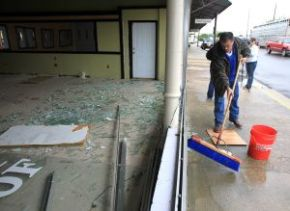 West, Texas: Jason Thomas sweeps up broken glass from a vacant store front in downtown West.